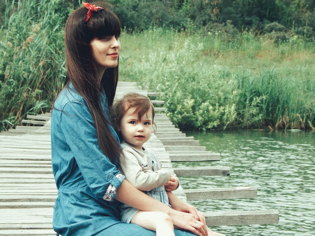 Peaceful woman sitting on a bridge with her young child.